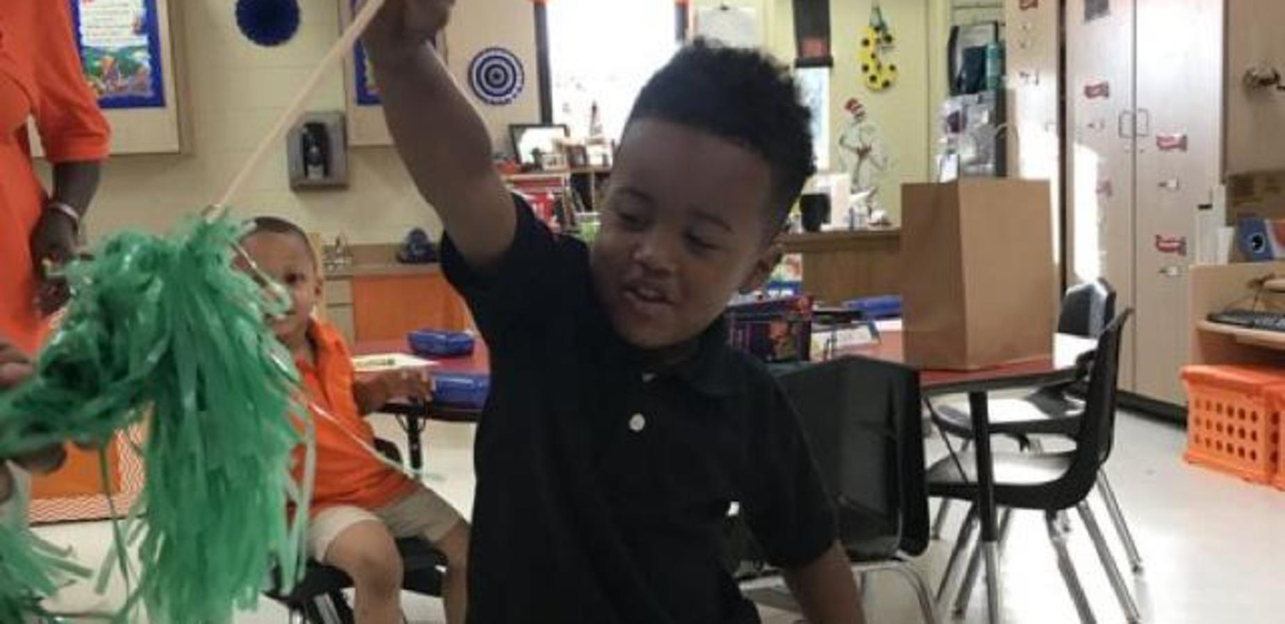 Student waving a green pompom.