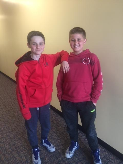 two boys in red sweatshirts smile for camera