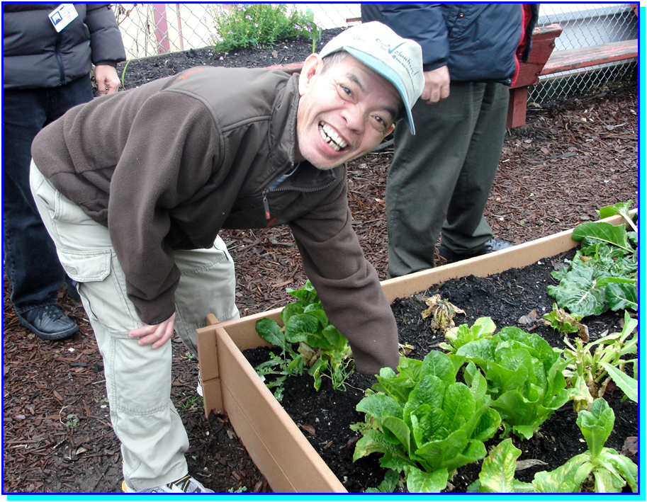 An adult student gesturing to a plant in a raised bed garden.