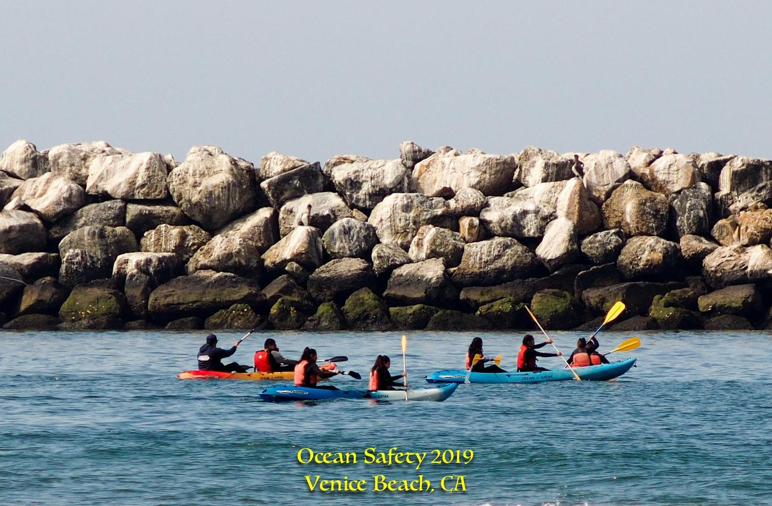 students in ocean water learning how to kayak