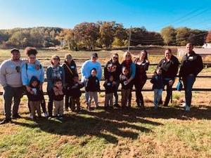 parents lined up with their kids with the pumpkin patch background
