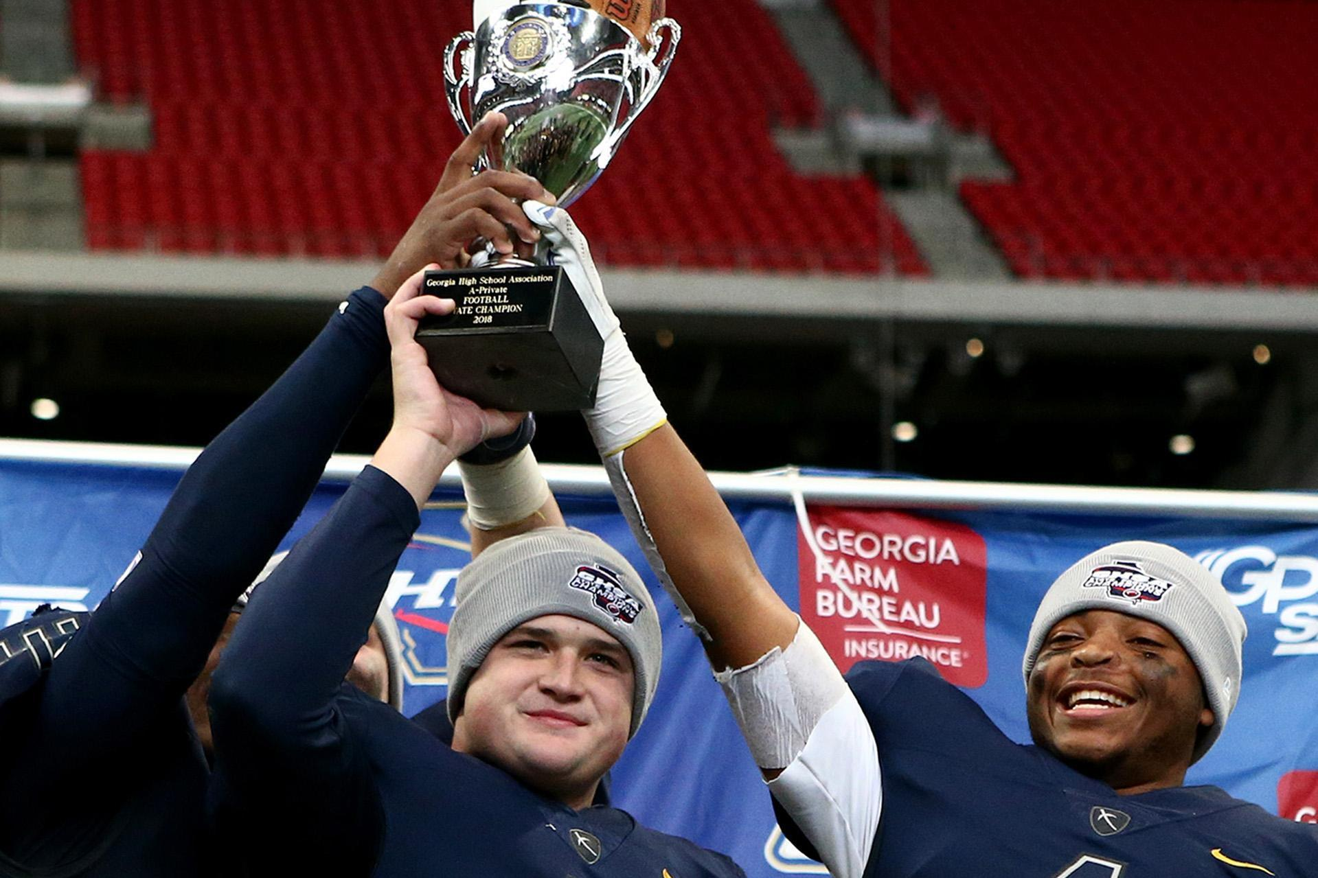ELCA Football players holding ghsa state championship trophy