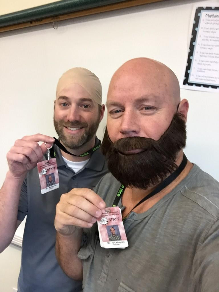 two men in bald cap and fake beards with each other's badges celebrate looking like twins