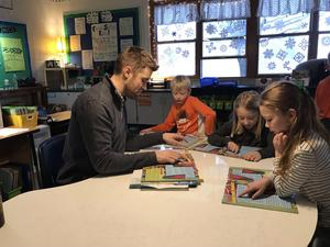 Second-grade teacher Nathan Fischer works with Luke Kaechele, Emery Berg and Maggie McKeown in a small-group lesson.