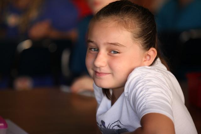 girl in class smiling at camera