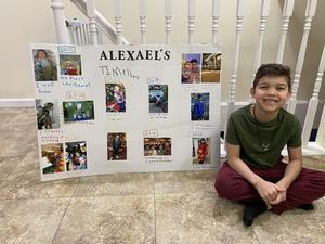 Alexael sitting next to his timeline poster
