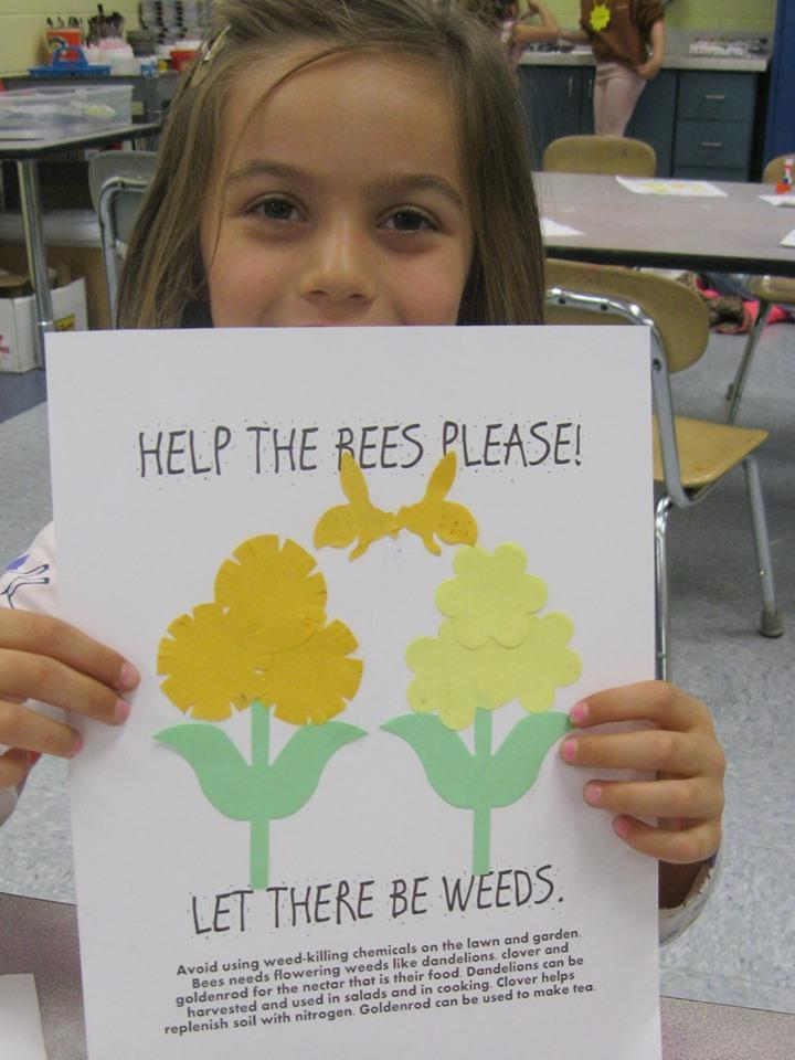 Child holding arts and craft with drawing of a bee