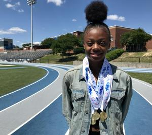 Jayla stands on the Airport High tracks,  wearing some of her state medals