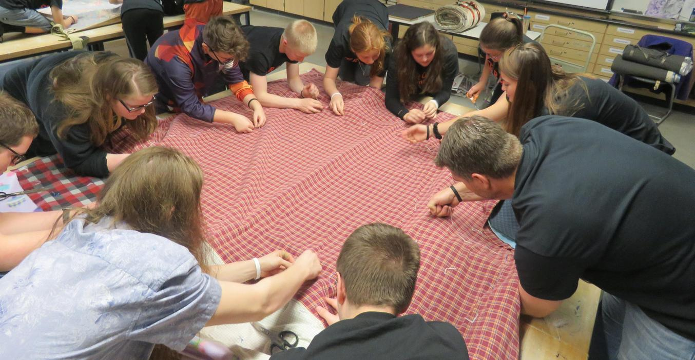 TKHS students sew blankets together to make sleeping bags for the homeless.