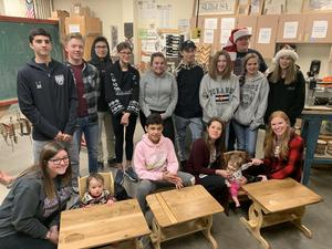 Woodworking students with toddlers in the tables and chairs.