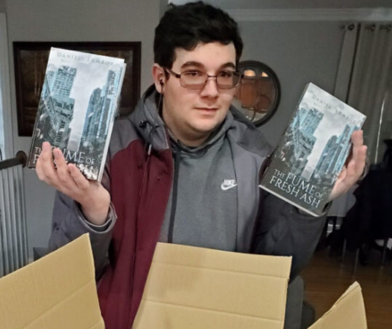 boy stands by table with box full of books he wrote