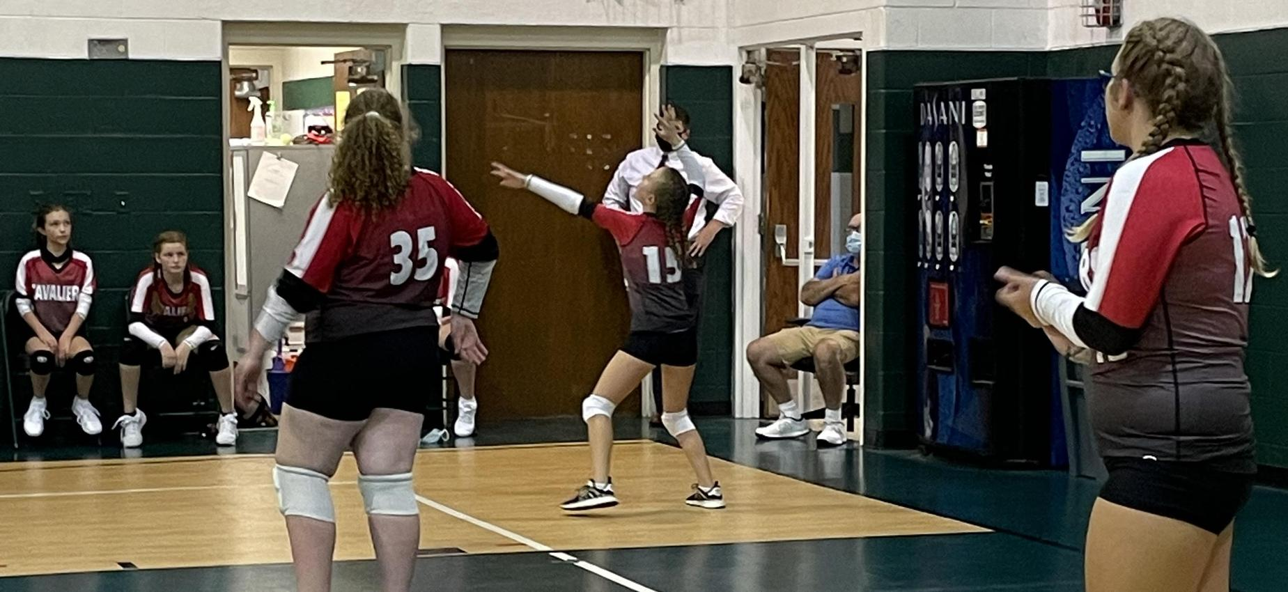 Volleyball players play in a gym.