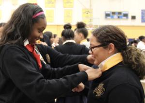 senior helping freshman at gold ties ceremony