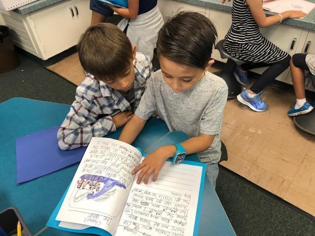 One student sharing his writing piece with another student