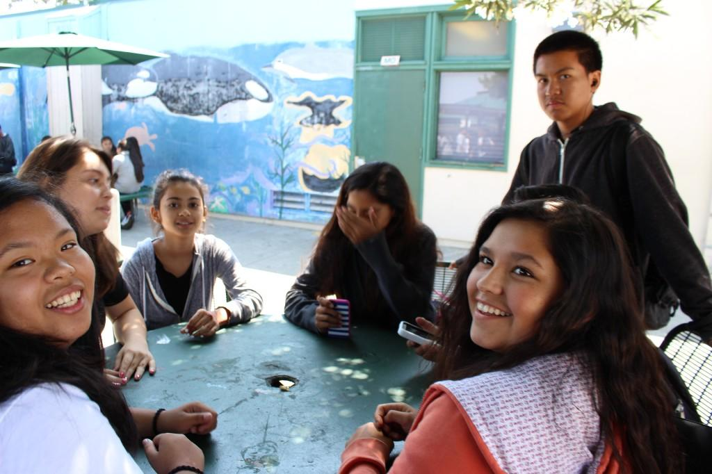 students surround a green table on the Bridges campus