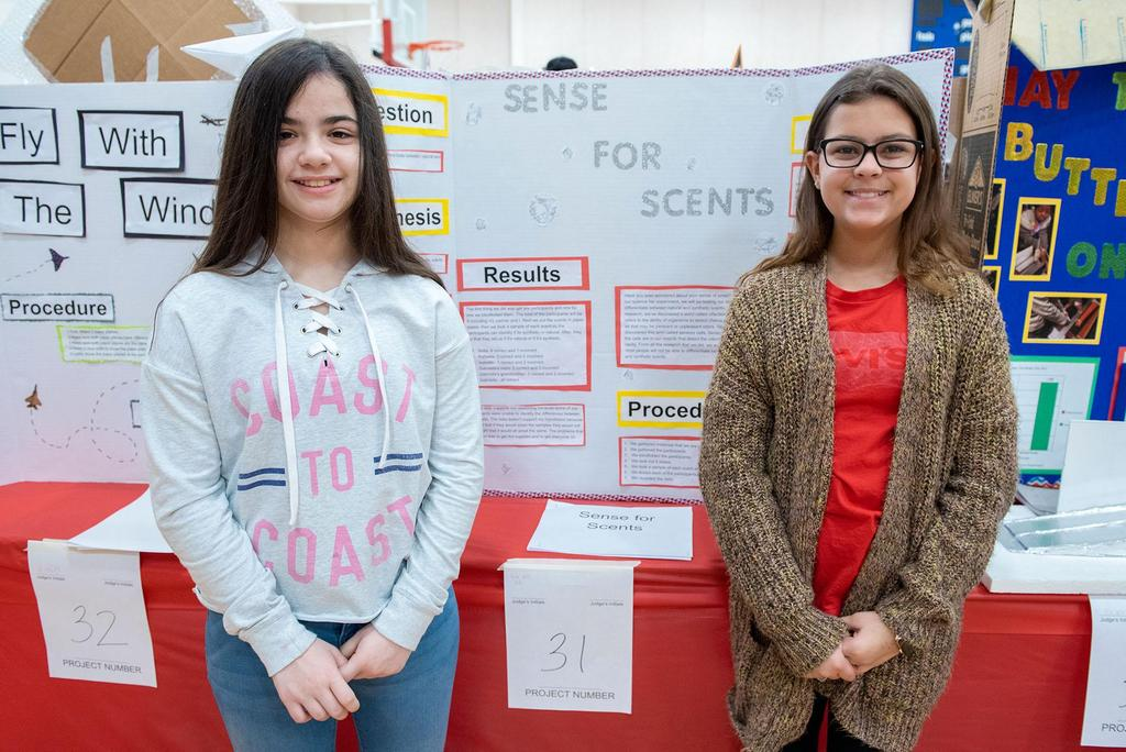 Two students stand in front of their project called Sense for Scents