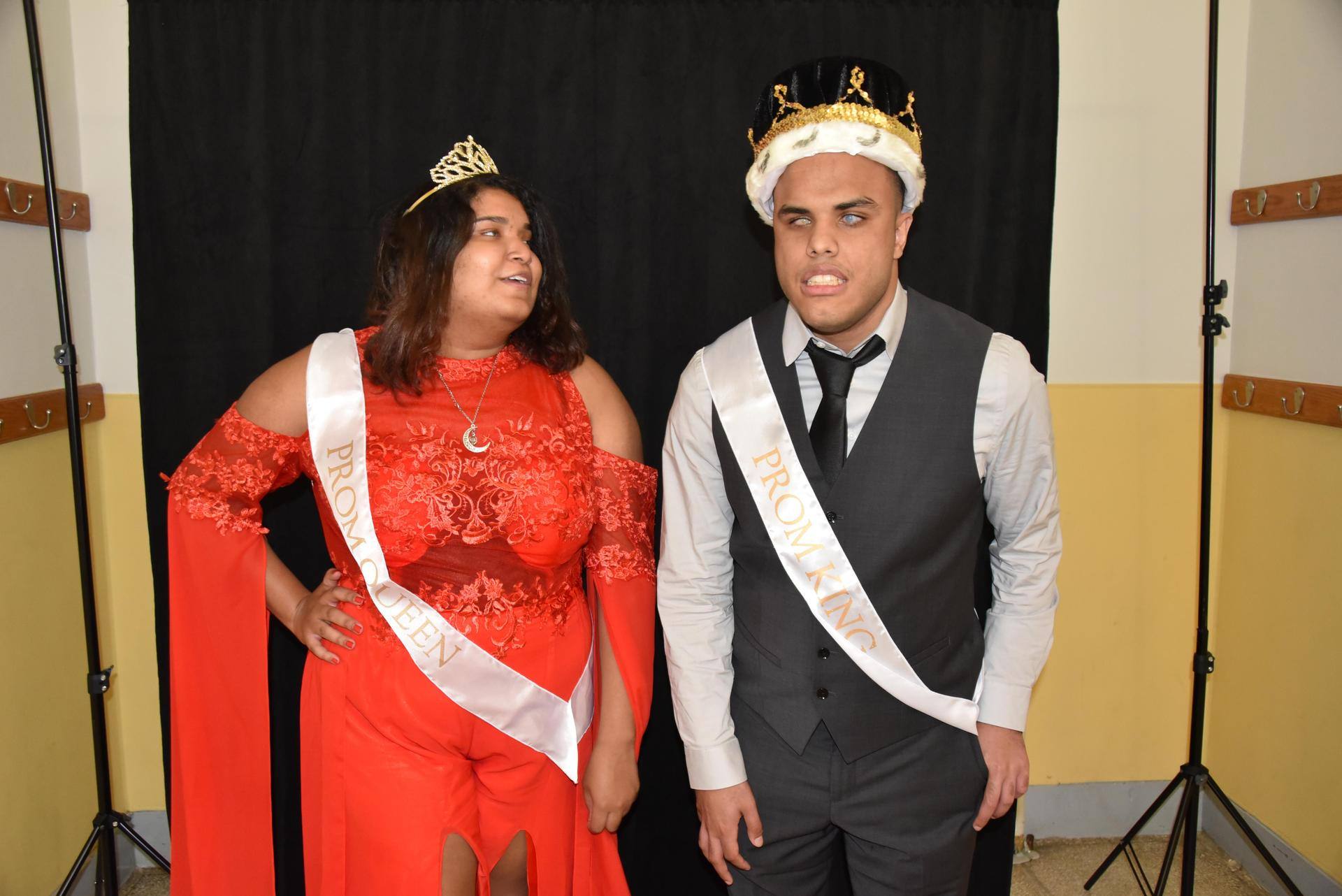 The prom queen and king pose for a photo, wearing crowns and sashes