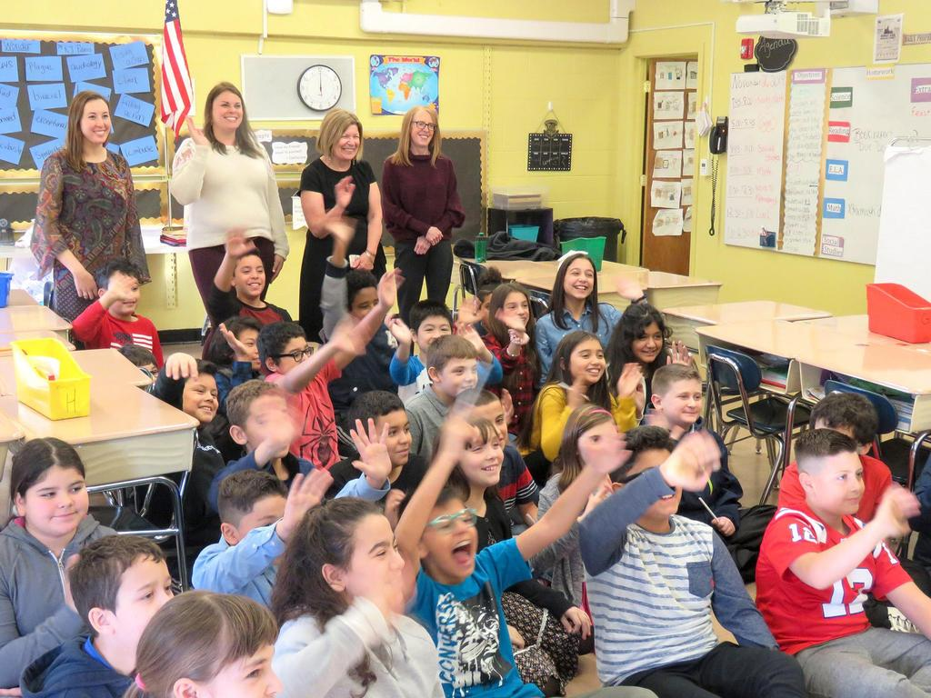 "The Webster School fifth graders enthusiastically wave their arms as they take part in a promo for NewsCenter 5's ""Weekend EyeOpener"""