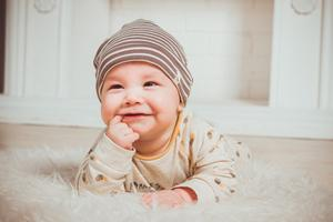 Baby smiling on blanket.
