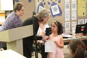 Kindergarten student reading Essay. Superintendent holding microphone