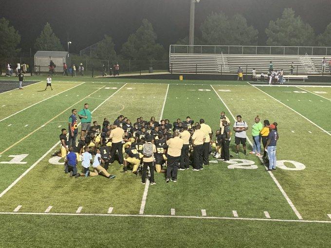 Football team huddled on the field