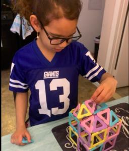 Girl building 3D structure puzzle