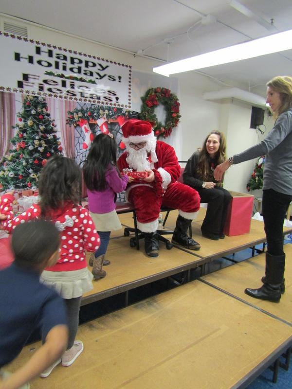 santa handing out presents to the little girls
