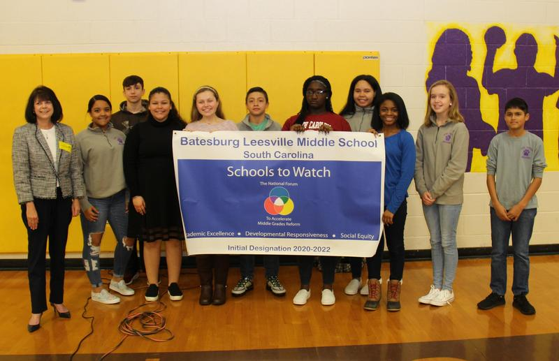 Tina Jamison, Executive Director of the South Carolina Association for Middle Level Education (far left), presents the official School to Watch designation banner to students at Batesburg-Leesville Middle School on Wednesday, March 4th.