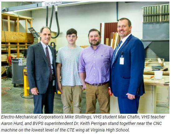 Electro-Mechanical Corporation's Mike Stollings, VHS student Max Chafin, VHS teacher Aaron Hurd, and BVPS superintendent Dr. Keith Perrigan stand together near the CNC machine on the lowest level of the CTE wing at Virginia High School.
