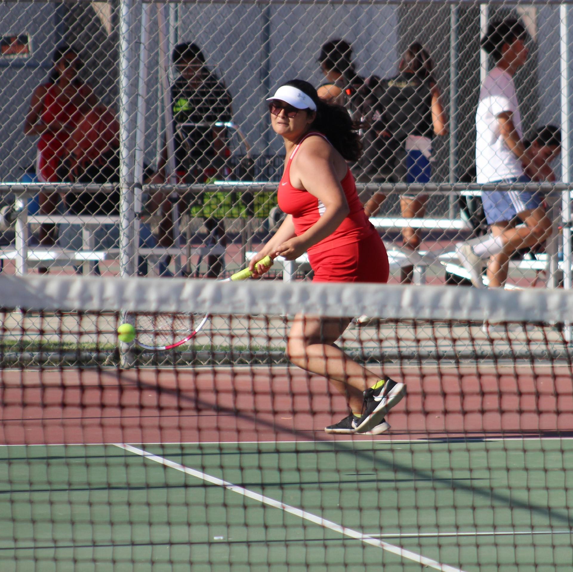 Girls playing tennis against Golden Valley