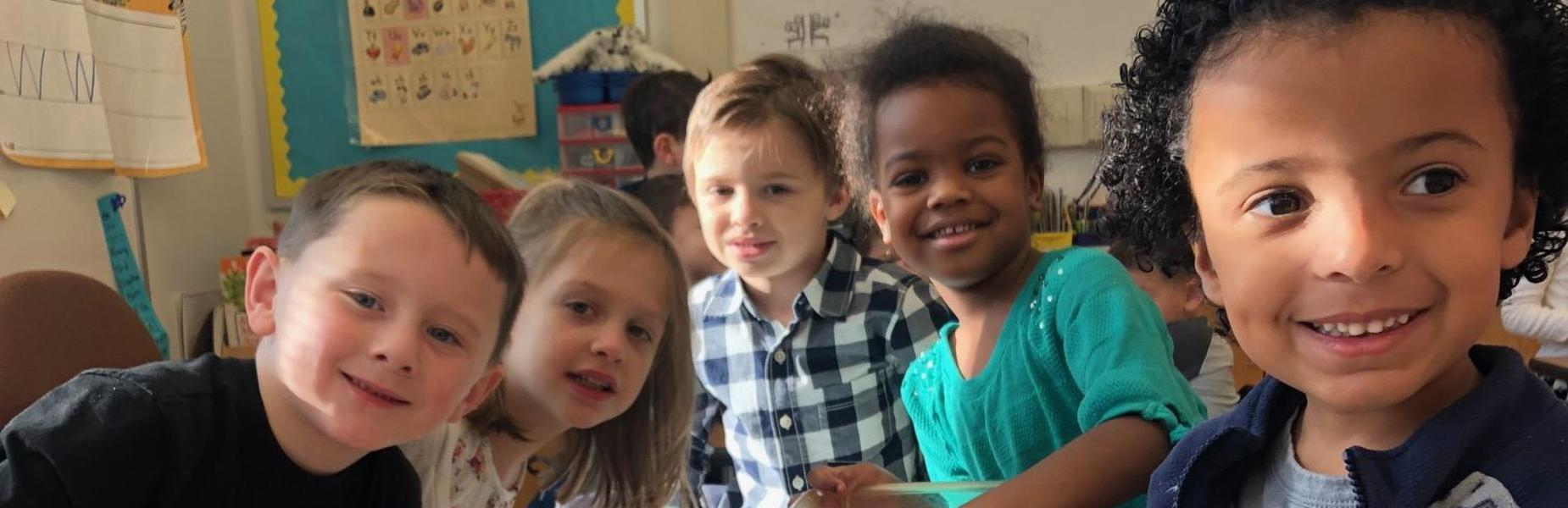 Kindergartners take a break from classroom activity to smile for the camera.