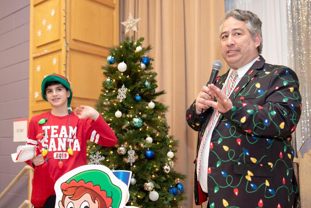 Principal Alex Naumann, in a sports coat adorned with a Christmas-light design, welcomes guests to Breakfast with Santa