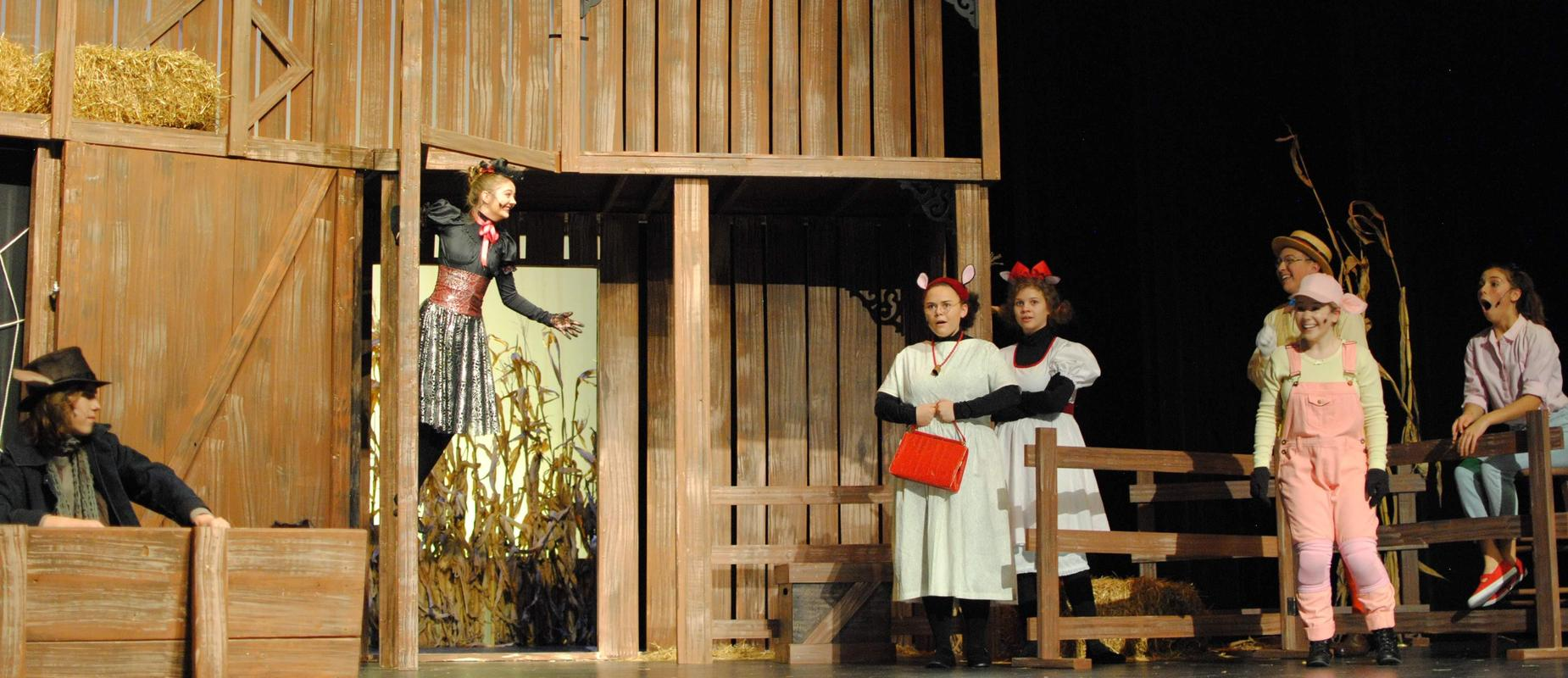 Charlotte's Web cast on stage with fence and barn props