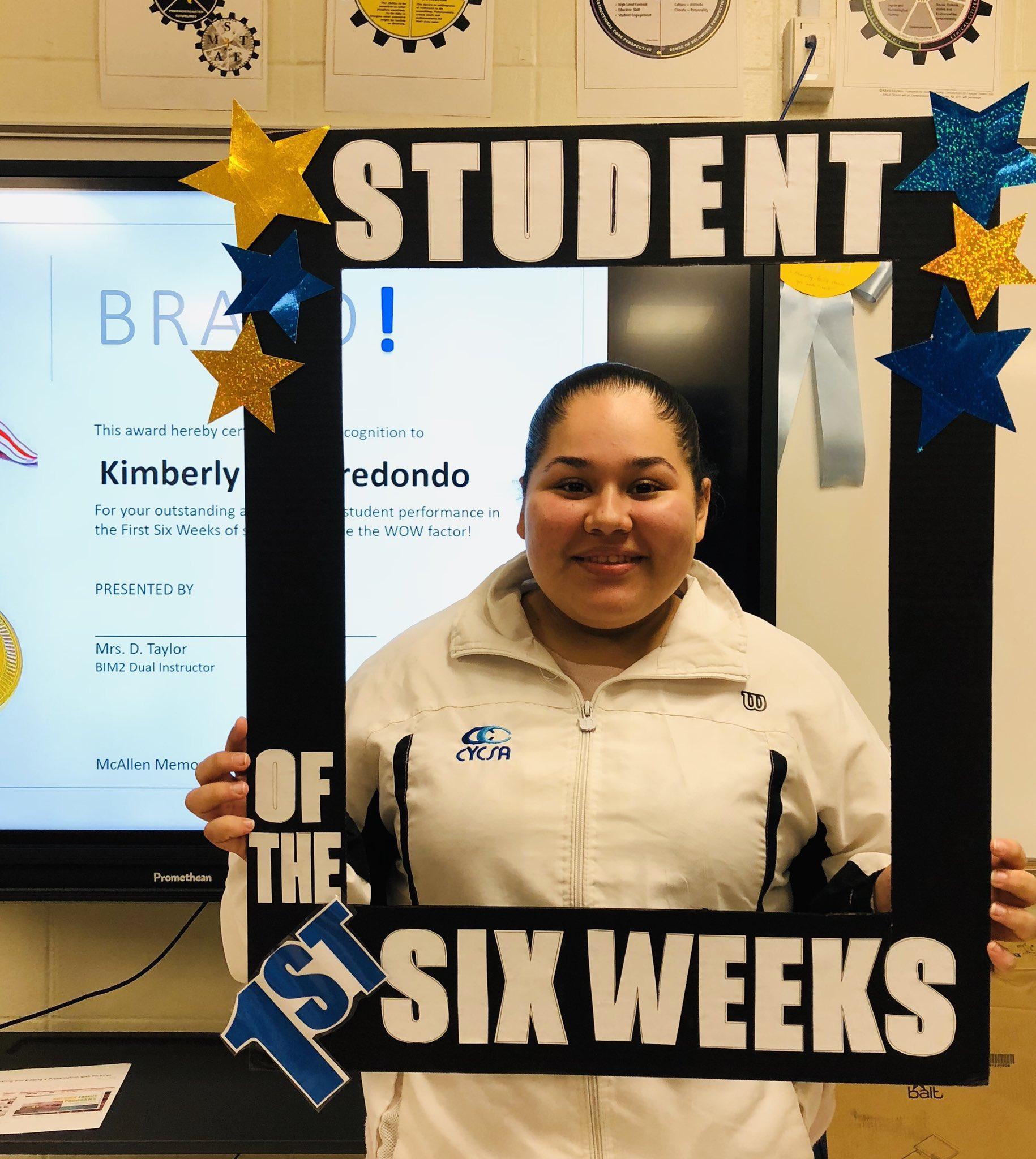 student holding award frame