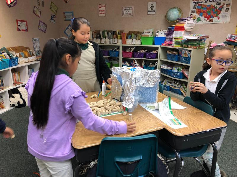 students working together to design and build a structure that can withstand a simulated natural disaster, image 4