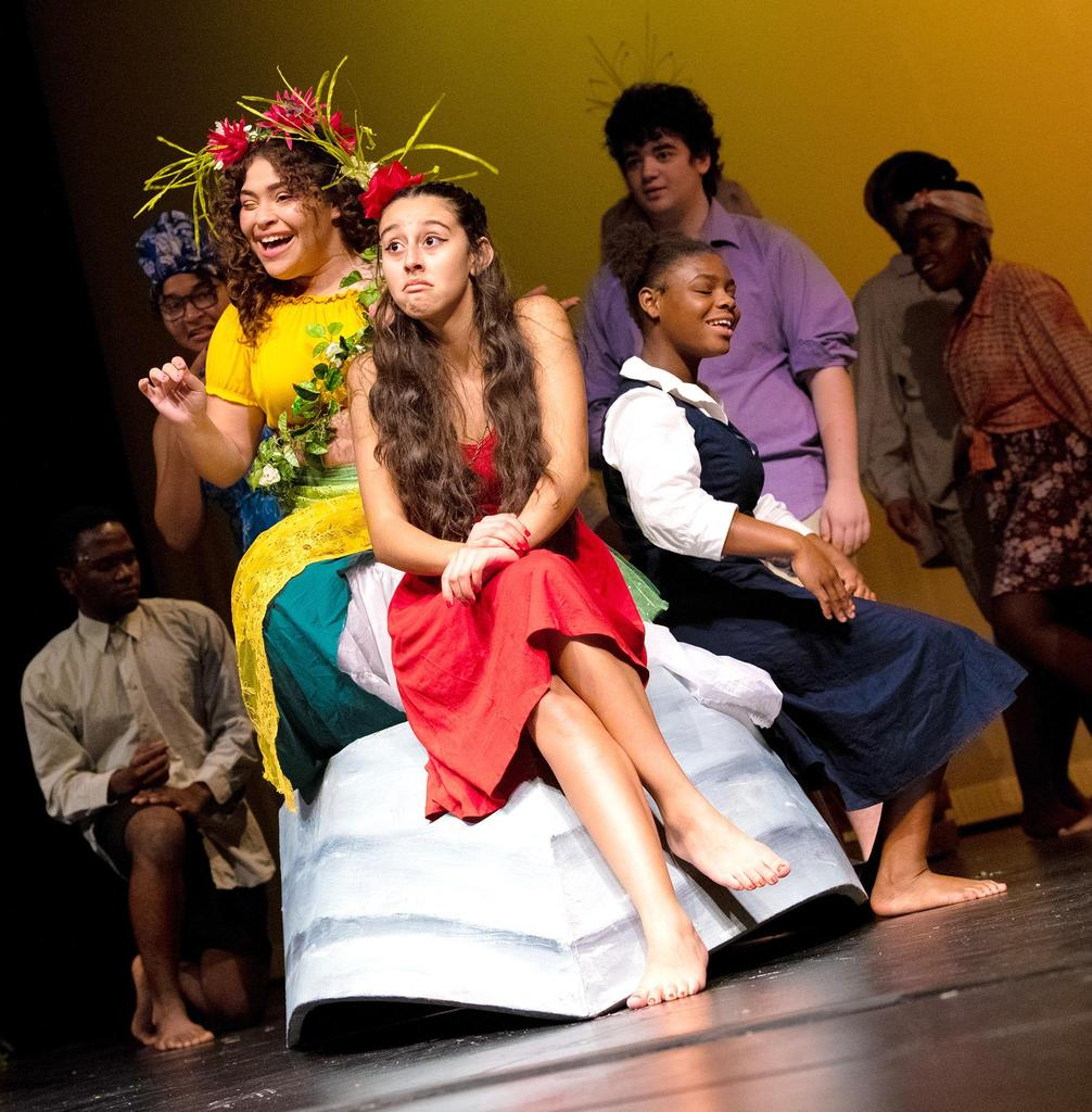 A smiling Dacia Eugene, as Asaka, Mother of the Earth and Rae Previlon (Little Girl) are to either side of a seated Jhalyshka Feliciano (Ti Moune), who's wearing a bemused expression