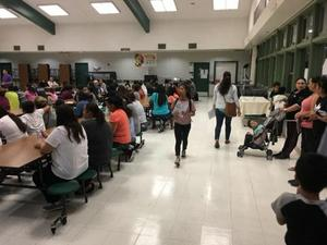 students and parents sitting at tables and standing in the cafeteria at Bridges Academy