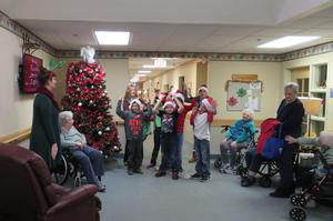 A crowd of Carveth Village residents fill the hallway as students sing Christmas carols.