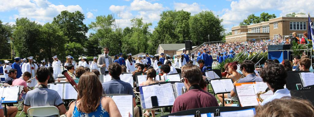 Photo of back of WHS band/orchestra performing graduation processional as 12th graders process onto the field.