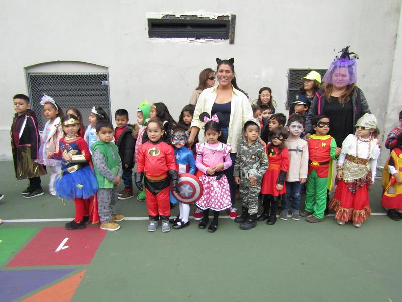 Kitty Cat teacher standing by her pre-k classroom in their costumes