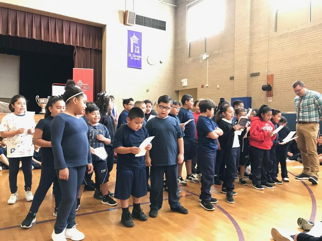 3rd grade students sing their cheer in the gym