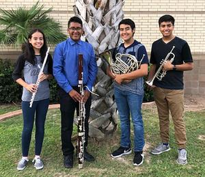 four students holding their instruments.