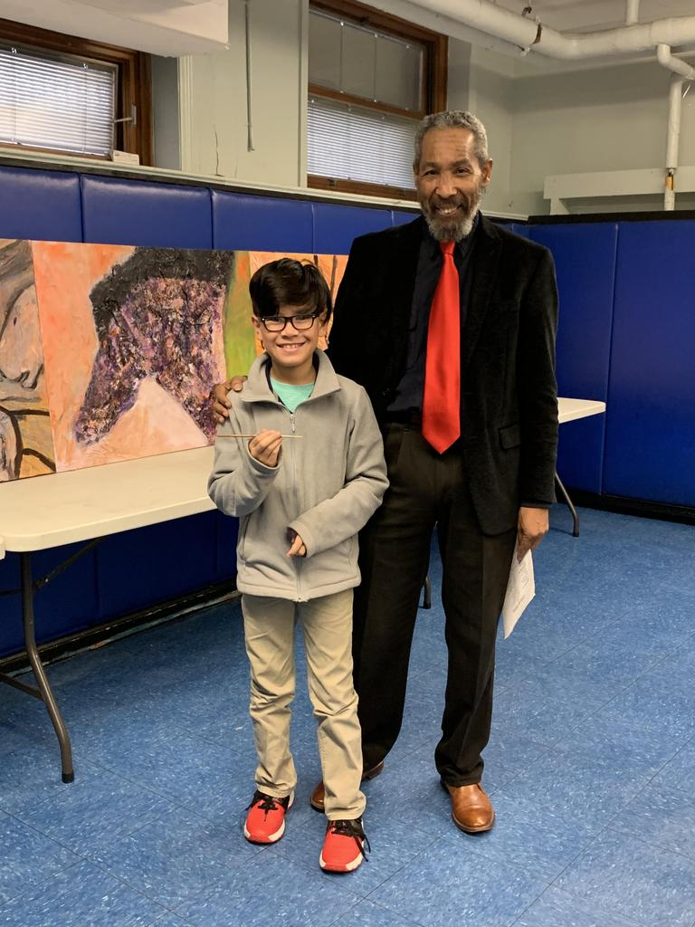 Artist Brooks with a boy wearing glasses and holding and artist pencil