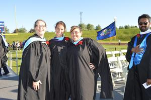 3 female class advisors pose together on the dais after the commencement