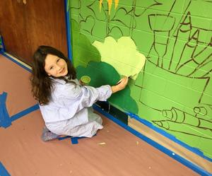 Second and third graders at Jefferson Elementary School help to transform school hallways into a magical scene of the many events that take place each year.  A student is pictured here painting the mural.