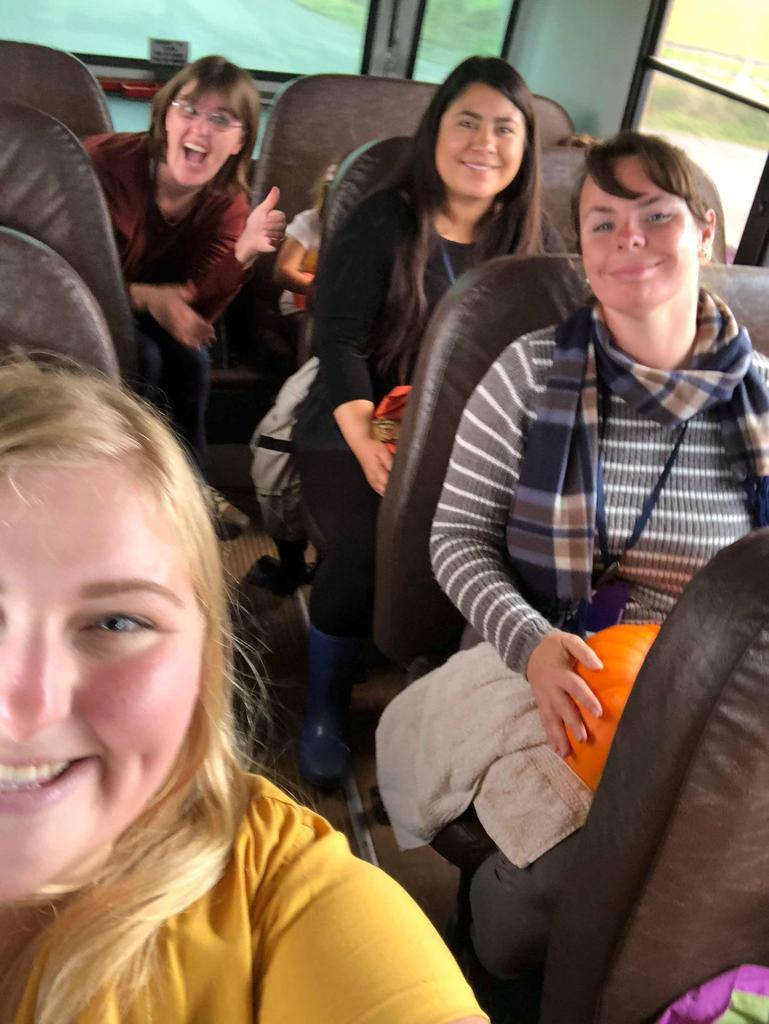 4 Adults on a school bus, smiling