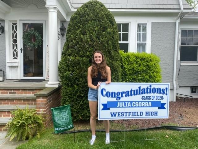 Photo of Westfield High School student with graduation lawn sign.
