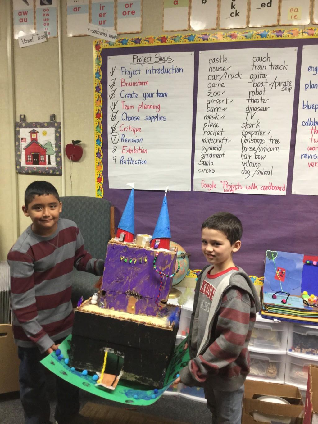 students holding a castle they built