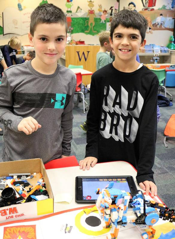 Two Wilson students show off the Lego robot they built and programmed during an afterschool STEAM session.