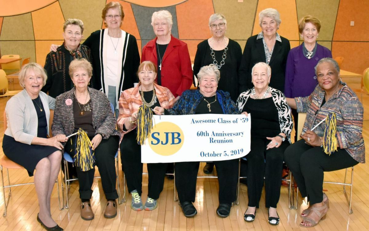 women sitting behind a blue and gold banner